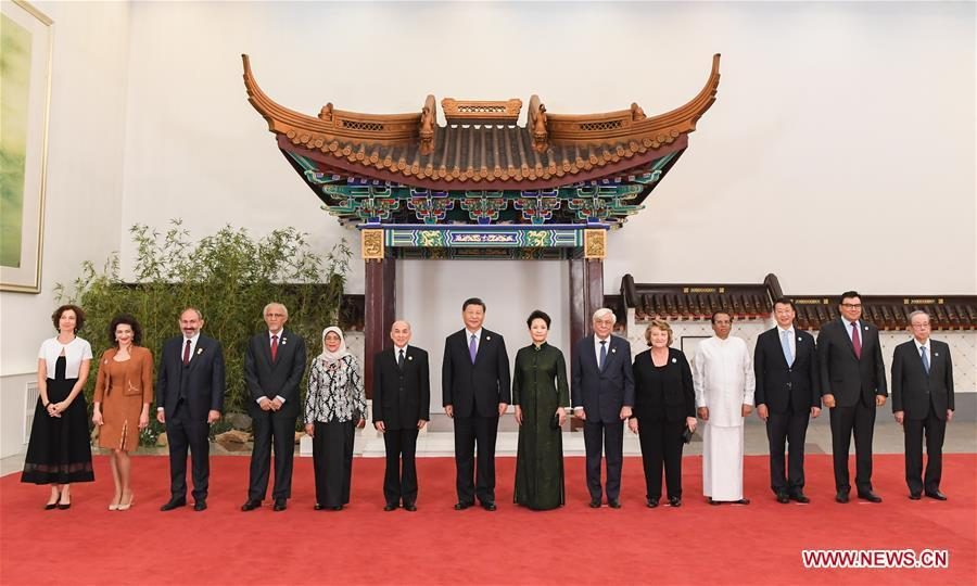 Chinese President Xi Jinping (7th L) and his wife Peng Liyuan (8th L) pose for group photos with guests who are in Beijing to attend the Conference on Dialogue of Asian Civilizations (CDAC), on May 14, 2019. Xi and his wife Peng Liyuan hosted a banquet in Beijing on Tuesday evening in honor of the guests. (Xinhua/Rao Aimin)
