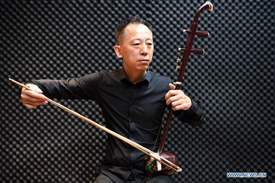 Erhu performer Zhang Zhijun plays Erhu in Lanzhou, northwest China\'s Gansu Province, May 13, 2019. Erhu, sometimes known as the Chinese violin or Chinese two-stringed fiddle, is a Chinese traditional two-stringed bowed musical instrument. It is used as a solo instrument as well as in small ensembles and large orchestras. Erhu, traced back to ancient Chinese Tang dynasty (618-907), is now used in both traditional and contemporary music arrangements, such as in pop, rock and jazz. The famous solo pieces include Er Quan Ying Yue (Two Springs Reflecting the Moon) by Abing and Sai Ma (Horse Race) by Huang Haihuai. (Xinhua/Fan Peishen)