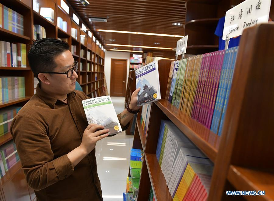 Sangay Tenzin reads books at a book store of the Beijing Language and Culture University in Beijing, capital of China, May 14, 2019. Sangay Tenzin, a Bhutanese student of Beijing Language and Culture University, is one of the photographers whose work was accepted by an exhibition themed \