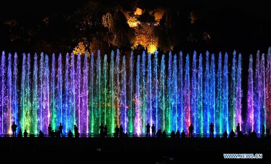 Tourists enjoy a light show at the Olympic Forest Park in Beijing, capital of China, May 14, 2019. Roads and buildings were illuminated Tuesday evening before the upcoming Conference on Dialogue of Asian Civilizations (CDAC) in Beijing. (Xinhua/Ju Huanzong)