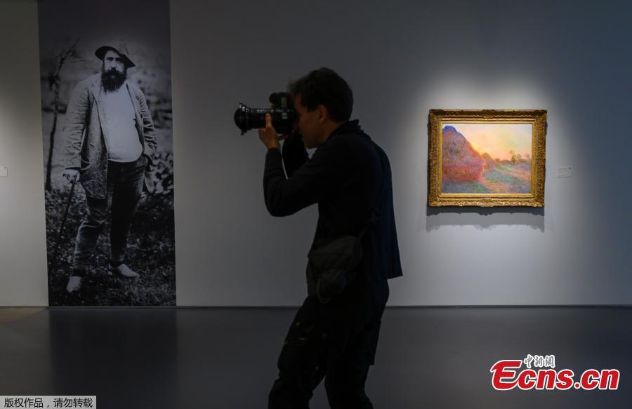 In this file photo taken on May 02, 2019, A photographer takes photos during a media preview, for Sotheby\'s Impressionist & Modern Art and Contemporary Art auctions, in New York. In the background is a picture of Claude Monet and one his famed Haystacks paintings. A Claude Monet painting from his \