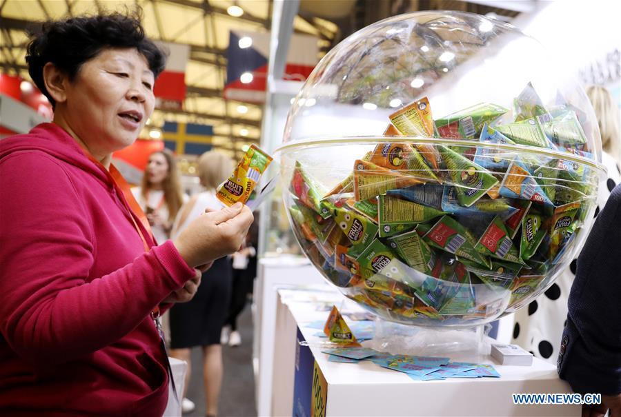 A visitor views exhibits in front of the booth of a Ukrainian juice exhibitor during the 20th SIAL China in Shanghai, east China, May 14, 2019. The 20th SIAL China, an international food and beverage exhibition, kicked off at Shanghai New International Expo Center on Tuesday. The exhibition has attracted nearly 4,300 exhibitors from different countries and regions . (Xinhua/Fang Zhe)