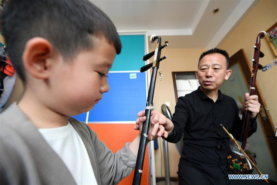 Erhu performer Zhang Zhijun (R) instructs his student in Lanzhou, northwest China\'s Gansu Province, May 13, 2019. Erhu, sometimes known as the Chinese violin or Chinese two-stringed fiddle, is a Chinese traditional two-stringed bowed musical instrument. It is used as a solo instrument as well as in small ensembles and large orchestras. Erhu, traced back to ancient Chinese Tang dynasty (618-907), is now used in both traditional and contemporary music arrangements, such as in pop, rock and jazz. The famous solo pieces include Er Quan Ying Yue (Two Springs Reflecting the Moon) by Abing and Sai Ma (Horse Race) by Huang Haihuai. (Xinhua/Fan Peishen)