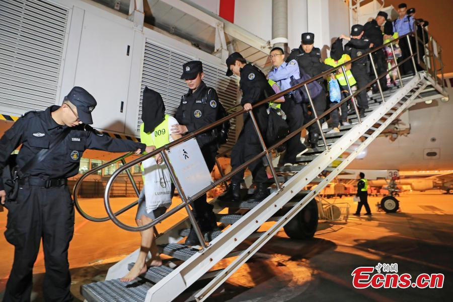 Police escort suspects caught in a social network and telecommunication fraud bust as they arrive at Pudong International Airport in Shanghai, May 14, 2019. Police detained the 57 suspects in Danzhou City of South China's Hainan Province and then transported them to Shanghai as investigations continue.  (Photo: China News Service/Yin Liqin)