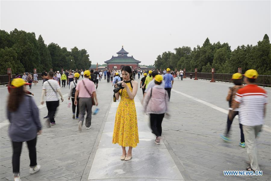Feng Ganyu checks the pictures she took at the Temple of Heaven in Beijing, capital of China, May 11, 2019. A photographic exhibition themed \
