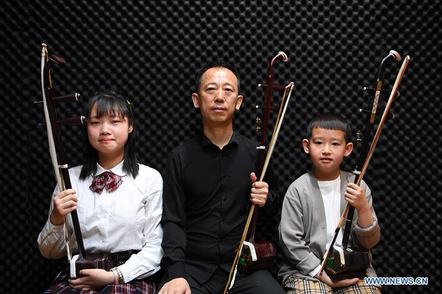Erhu performer Zhang Zhijun (C) poses for a group photo with his students in Lanzhou, northwest China\'s Gansu Province, May 13, 2019. Erhu, sometimes known as the Chinese violin or Chinese two-stringed fiddle, is a Chinese traditional two-stringed bowed musical instrument. It is used as a solo instrument as well as in small ensembles and large orchestras. Erhu, traced back to ancient Chinese Tang dynasty (618-907), is now used in both traditional and contemporary music arrangements, such as in pop, rock and jazz. The famous solo pieces include Er Quan Ying Yue (Two Springs Reflecting the Moon) by Abing and Sai Ma (Horse Race) by Huang Haihuai. (Xinhua/Fan Peishen)
