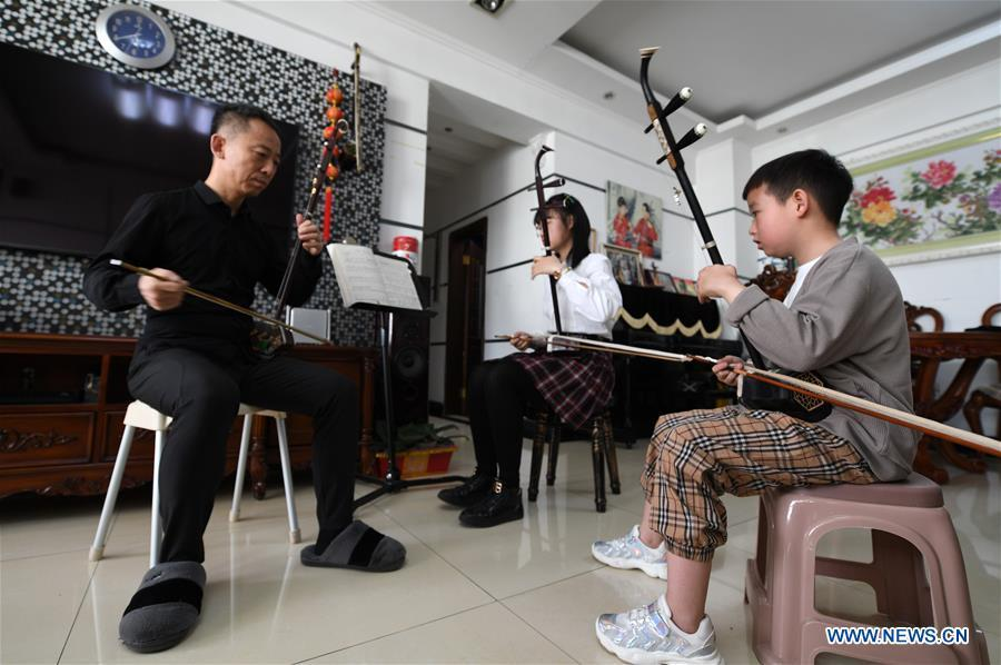 Erhu performer Zhang Zhijun (1st L) instructs his students in Lanzhou, northwest China\'s Gansu Province, May 13, 2019. Erhu, sometimes known as the Chinese violin or Chinese two-stringed fiddle, is a Chinese traditional two-stringed bowed musical instrument. It is used as a solo instrument as well as in small ensembles and large orchestras. Erhu, traced back to ancient Chinese Tang dynasty (618-907), is now used in both traditional and contemporary music arrangements, such as in pop, rock and jazz. The famous solo pieces include Er Quan Ying Yue (Two Springs Reflecting the Moon) by Abing and Sai Ma (Horse Race) by Huang Haihuai. (Xinhua/Fan Peishen)