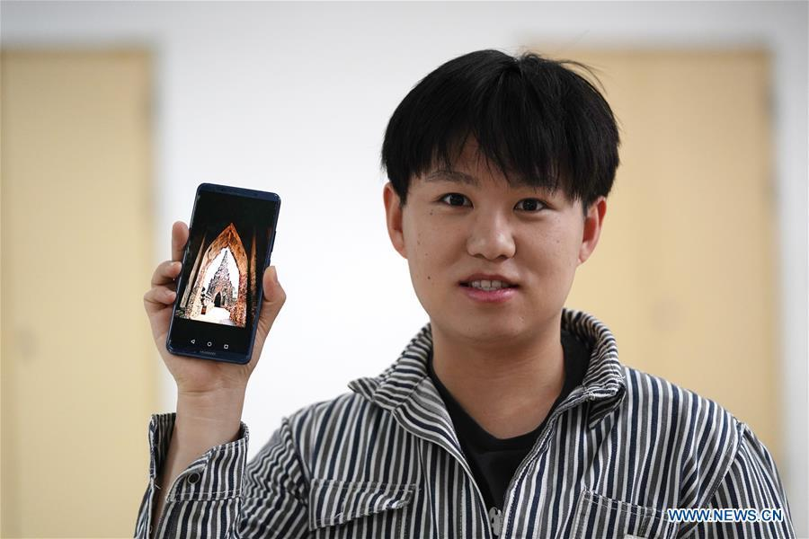 Ratjirot Aekkawat shows his photo of the historical site of Ayutthaya Dynasty in Beijing, capital of China, May 12, 2019. Ratjirot Aekkawat is of mixed blood from China and Thailand. He came to study in China as a junior student and now he is a postgraduate student of the Peking University. He always talks about his experience in China with relatives and friends. He has witnessed the development of China in recent years, during which the environment and local governments\' working efficiencies have been greatly improved. Chinese and Thai cultures are influenced with each other. Many Thai people celebrate the Spring Festival every year and lots of Chinese go to Thailand for tourism. The photo of the historical site of Ayutthaya Dynasty taken by Ratjirot Aekkawat will be displayed in a photographic exhibition \