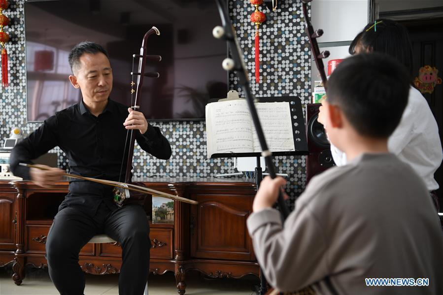 Erhu performer Zhang Zhijun (L) instructs his students in Lanzhou, northwest China\'s Gansu Province, May 13, 2019. Erhu, sometimes known as the Chinese violin or Chinese two-stringed fiddle, is a Chinese traditional two-stringed bowed musical instrument. It is used as a solo instrument as well as in small ensembles and large orchestras. Erhu, traced back to ancient Chinese Tang dynasty (618-907), is now used in both traditional and contemporary music arrangements, such as in pop, rock and jazz. The famous solo pieces include Er Quan Ying Yue (Two Springs Reflecting the Moon) by Abing and Sai Ma (Horse Race) by Huang Haihuai. (Xinhua/Fan Peishen)