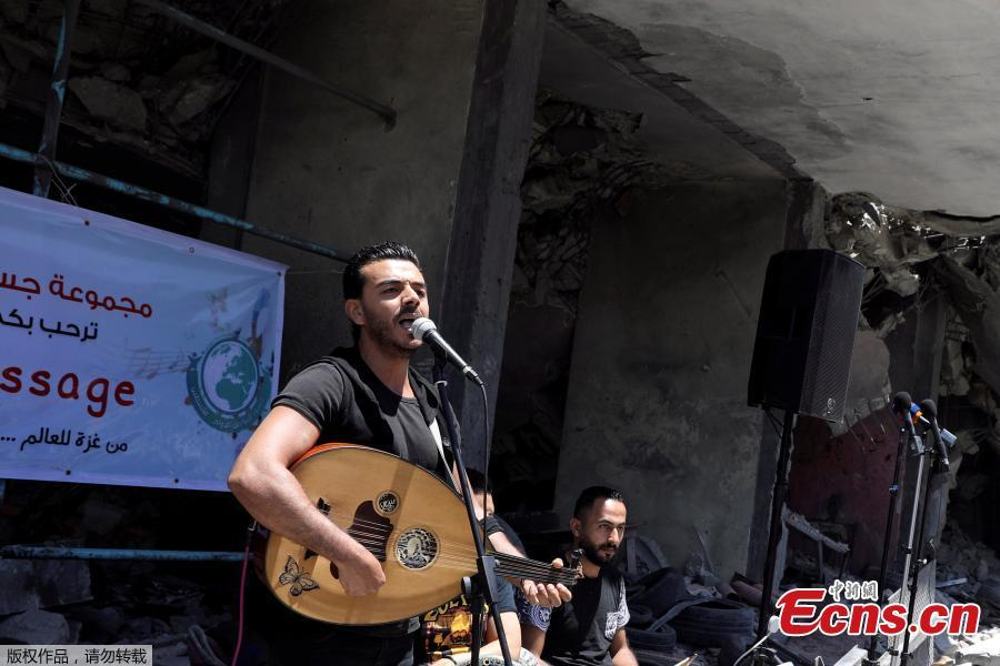 A Palestinian singer performs during a musical event calling to boycott the Eurovision Song Contest hosted by Israel, on the rubble of a building that was recently destroyed by Israeli air strikes, in Gaza City May 14, 2019. (Photo/Agencies)