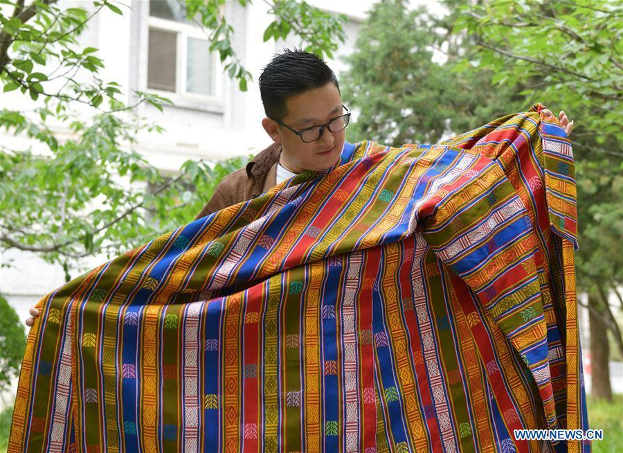 Sangay Tenzin displays traditional costumes made by his mother on the campus of the Beijing Language and Culture University in Beijing, capital of China, May 14, 2019. Sangay Tenzin, a Bhutanese student of Beijing Language and Culture University, is one of the photographers whose work was accepted by an exhibition themed \