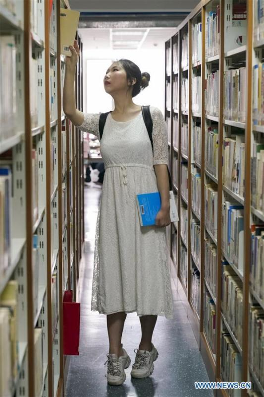 Feng Ganyu checks books in a library at Beijing Normal University in Beijing, capital of China, May 12, 2019. A photographic exhibition themed \