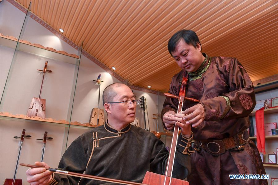 Baisu Gulang (R), a 37-year-old horse head fiddle maker, teaches his apprentice Yu Zhe to play horse head fiddle in Qian Golos Mongolian Autonomous County of Songyuan, northeast China\'s Jilin Province, May 15, 2019. Under his father\'s influence, Baisu Gulang has an ardent love in making and playing horse head fiddle, a traditional musical instrument favored by Mongolian ethnic group. He started learning to make horse head fiddle when he was 18 years old. In 2006, Baisu Gulang started a horse head fiddle making studio where he voluntarily teaches enthusiasts to make and play the instrument besides selling. (Xinhua/Zhang Nan)