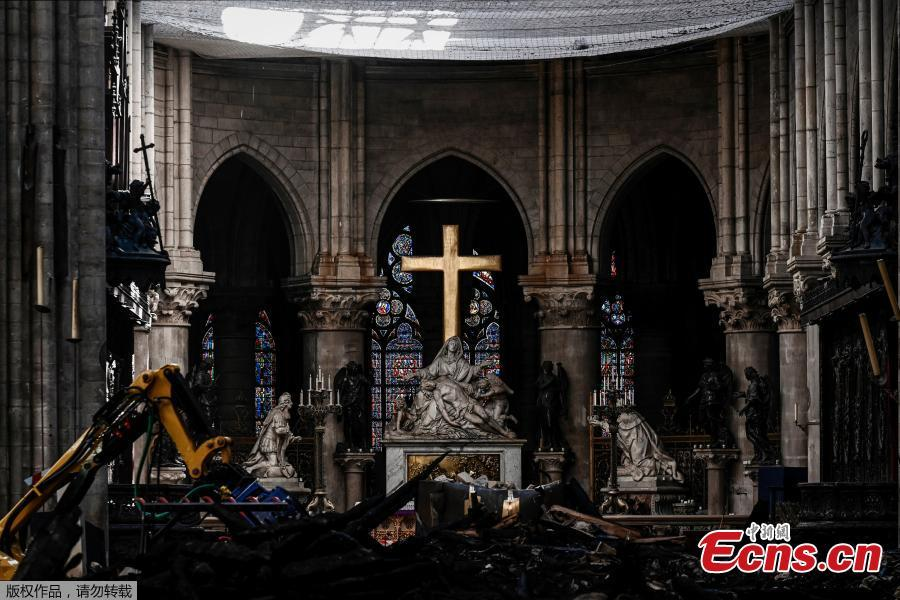 Rubble and the cross inside the Notre Dame de Paris Cathedral, Wednesday May 15, 2019 in Paris. French Culture Minister Franck Riester says that one month after a fire engulfed Notre Dame Cathedral, the edifice is still being made safe enough for restoration to begin. (Photo/Agencies)