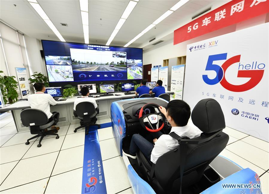 A technician controls a car at a driving simulation cabin in a lab during a test run in Chongqing, southwest China, May 15, 2019. A remote-controlled car powered by the 5G network completed a test run on Wednesday in Chongqing. During the test run, a remote operator was able to control the car while watching the live feed of road conditions supported by the 5G network. (Xinhua/Liu Chan)
