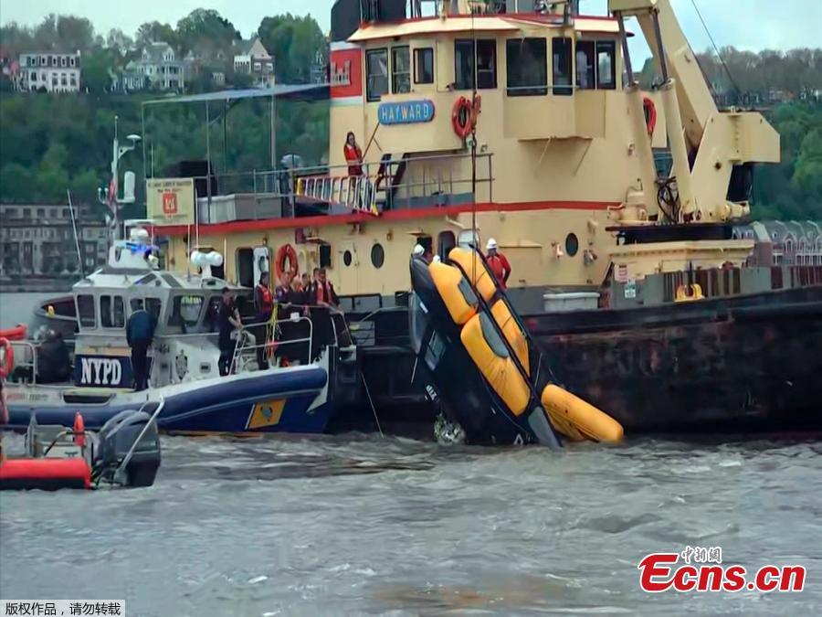A helicopter is loaded, by crane, onto a barge after it crashed into the Hudson River on May 15, 2019 in New York.  A helicopter crashed into the Hudson River on May 15 afternoon shortly after taking off from a Manhattan heliport, authorities said. The pilot, identified as Eric Morales, was rescued by a passing NY Waterway ferry a short time later. (Photo/Agencies)