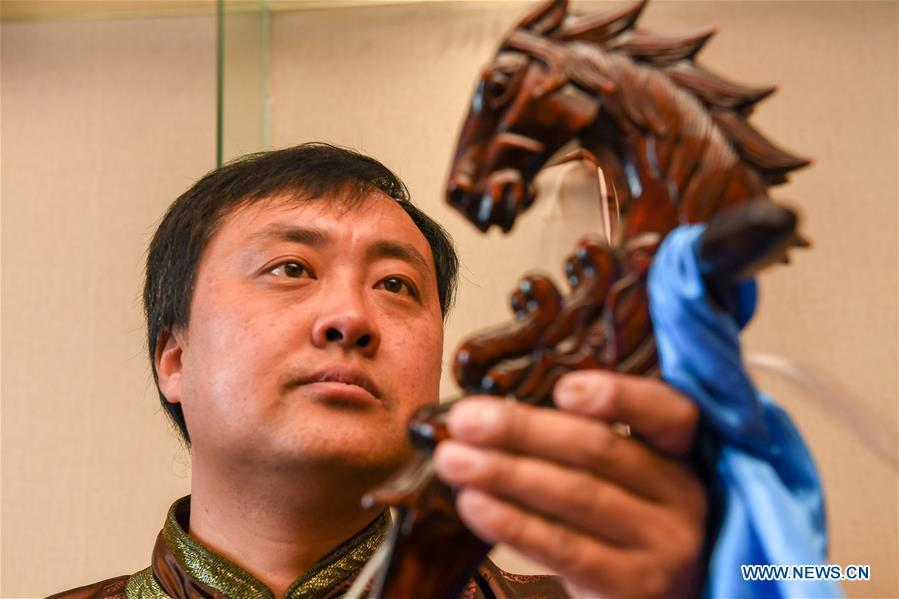 Baisu Gulang, a 37-year-old horse head fiddle maker, views a horse head fiddle in Qian Golos Mongolian Autonomous County of Songyuan, northeast China\'s Jilin Province, May 15, 2019. Under his father\'s influence, Baisu Gulang has an ardent love in making and playing horse head fiddle, a traditional musical instrument favored by Mongolian ethnic group. He started learning to make horse head fiddle when he was 18 years old. In 2006, Baisu Gulang started a horse head fiddle making studio where he voluntarily teaches enthusiasts to make and play the instrument besides selling. (Xinhua/Zhang Nan)