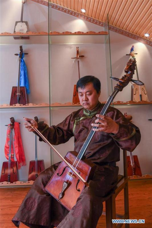 Baisu Gulang, a 37-year-old horse head fiddle maker, plays horse head fiddle in Qian Golos Mongolian Autonomous County of Songyuan, northeast China\'s Jilin Province, May 15, 2019. Under his father\'s influence, Baisu Gulang has an ardent love in making and playing horse head fiddle, a traditional musical instrument favored by Mongolian ethnic group. He started learning to make horse head fiddle when he was 18 years old. In 2006, Baisu Gulang started a horse head fiddle making studio where he voluntarily teaches enthusiasts to make and play the instrument besides selling. (Xinhua/Zhang Nan)