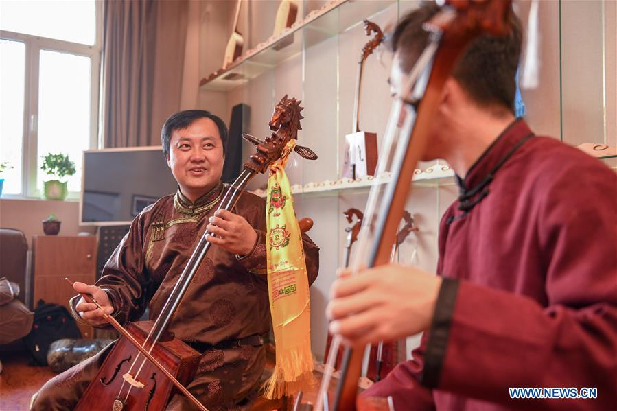 Baisu Gulang (L), a 37-year-old horse head fiddle maker, plays horse head fiddle in Qian Golos Mongolian Autonomous County of Songyuan, northeast China\'s Jilin Province, May 15, 2019. Under his father\'s influence, Baisu Gulang has an ardent love in making and playing horse head fiddle, a traditional musical instrument favored by Mongolian ethnic group. He started learning to make horse head fiddle when he was 18 years old. In 2006, Baisu Gulang started a horse head fiddle making studio where he voluntarily teaches enthusiasts to make and play the instrument besides selling. (Xinhua/Zhang Nan)