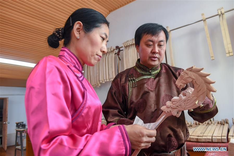 Baisu Gulang, a 37-year-old horse head fiddle maker, teaches his apprentice Zhang Hongxue to make a horse head fiddle in Qian Golos Mongolian Autonomous County of Songyuan, northeast China\'s Jilin Province, May 15, 2019. Under his father\'s influence, Baisu Gulang has an ardent love in making and playing horse head fiddle, a traditional musical instrument favored by Mongolian ethnic group. He started learning to make horse head fiddle when he was 18 years old. In 2006, Baisu Gulang started a horse head fiddle making studio where he voluntarily teaches enthusiasts to make and play the instrument besides selling. (Xinhua/Zhang Nan)