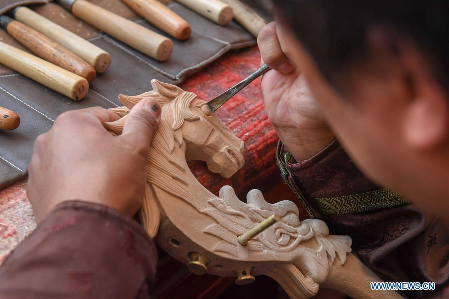 Baisu Gulang, a 37-year-old horse head fiddle maker, makes a horse head fiddle in Qian Golos Mongolian Autonomous County of Songyuan, northeast China\'s Jilin Province, May 15, 2019. Under his father\'s influence, Baisu Gulang has an ardent love in making and playing horse head fiddle, a traditional musical instrument favored by Mongolian ethnic group. He started learning to make horse head fiddle when he was 18 years old. In 2006, Baisu Gulang started a horse head fiddle making studio where he voluntarily teaches enthusiasts to make and play the instrument besides selling. (Xinhua/Zhang Nan)