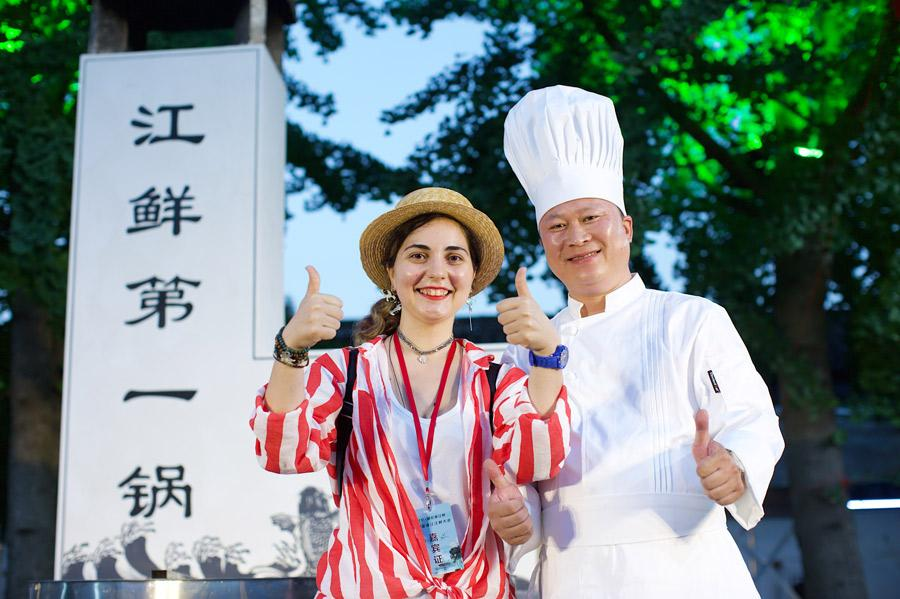 A tourist poses with a chef at a tasting event for fish from the Qiantang River in Hangzhou. (Photo provided to China Daily)