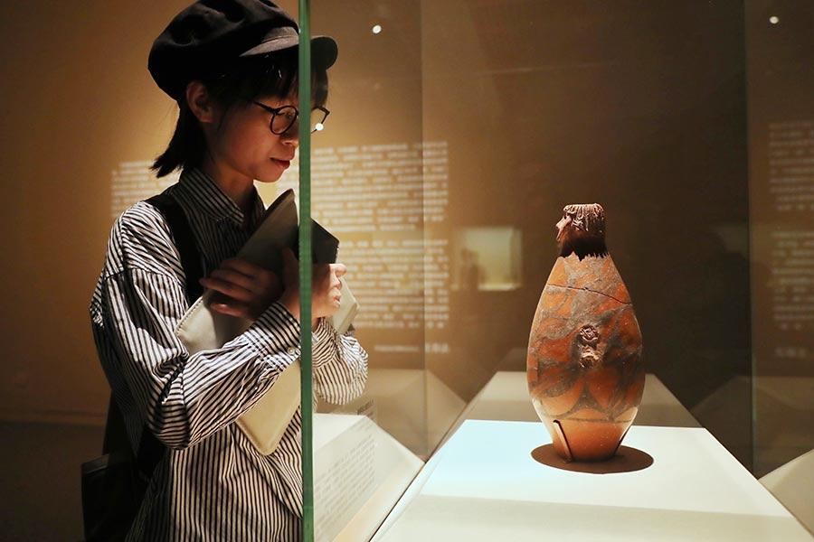A visitors looks at an artifact shown at exhibition Gateway to the Silk Road. (Photo/China Daily)