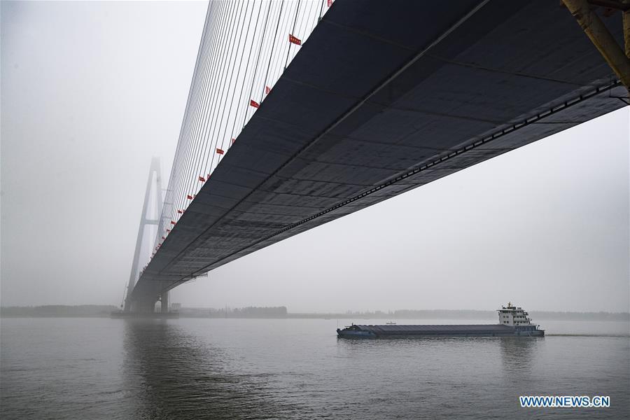 A boat passes under the Qingshan Yangtze River Bridge in Wuhan, central China\'s Hubei Province, May 16, 2019. The 7,548 meter-long Qingshan Yangtze River Bridge is now the widest bridge over Yangtze River. (Xinhua/Xiao Yijiu)