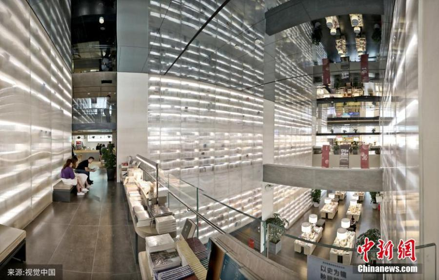 A bookstore featuring transparent bookcases in Xi'an, capital of Northwest China\'s Shaanxi province. Installed with three 12-meter-high such bookcases to show off reading materials, the bookstore offers customers an unique reading experience. (Photo/VCG)