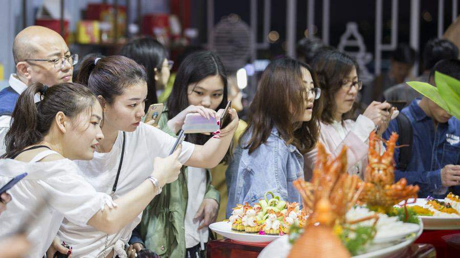 Visitors take pictures of dishes at the ongoing Taste of Hangzhou Asian Cuisine Festival. v During the festival, Hangzhou, famous for its Longjing tea, will hold a tea culture dialogue forum, inviting major Asian tea-producing countries such as Japan, Sri Lanka and India to participate in dialogue and exchanges. The festival will also host a forum promoting traditional Chinese food culture.  Exhibitions on traditional Chinese tableware and Asian cuisines will also be held.