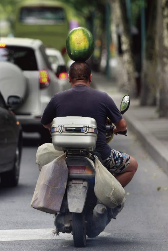 Hangzhou resident Wang Pinghua rides a motorcycle while balancing a watermelon on his head.   (Photo provided to China Daily)