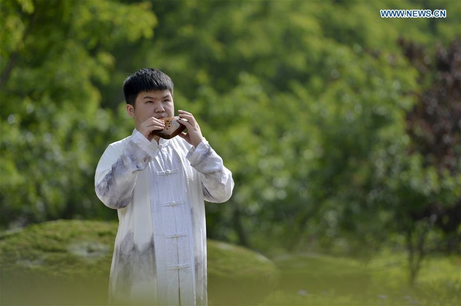 Li Xin plays the Ocarina, a flute-like instrument, in the fields in Xingtai, north China\'s Hebei Province, May 14, 2019. Ocarina is a wind musical instrument typically having an enclosed oval body with finger holes and a projecting mouthpiece. It is traditionally made of clay or ceramic, but other materials including wood and horn are used. It is an ancient instrument and can be traced back to many different cultures. (Xinhua/Mu Yu)