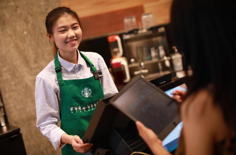 An employee able to communicate in sign language works the counter at Starbucks China\'s first store with sign language capability in Guangzhou\'s Yuexiu district, May 19, 2019. (Photo provided to chinadaily.com.cn)  For hearing impaired customers at a Starbucks in Guangzhou\'s Yuexiu district, ordering coffee can be much easier. Starbucks China on Sunday opened its first store with sign language capability in the city\'s oldest downtown area to offer more possibilities to the deaf and hard of hearing community.  The store employs people with hearing challenges and provides equal training opportunities. All employees in the store are professional baristas and can communicate in sign language.  The store also is aimed at raising awareness and understanding of deaf and hearing impaired experiences in the workplace, according to Starbucks.  Starbucks employs over 100 people with special needs in China.  To nurture talent and create more opportunities for the deaf workforce, Starbucks has partnered with the Guangdong Deaf People Association to offer professional skills training and sign language courses.  \