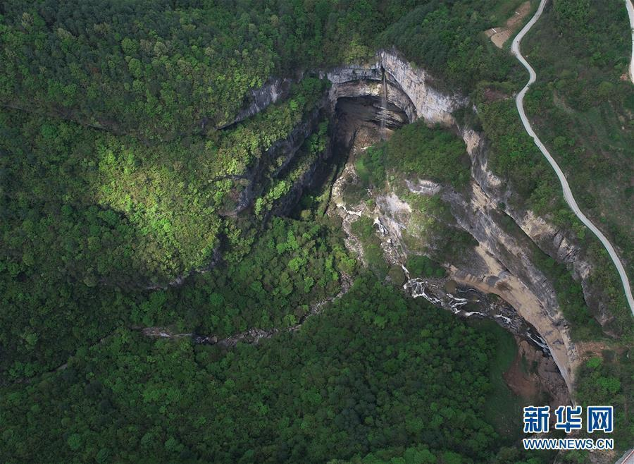 An aerial photo shows a waterfall in Didonghe Tiankeng, a giant karst sinkhole at Huoshizi Village of Ningqiang County in Hanzhong, northwest China\'s Shaanxi Province. With a maximum depth of 340 meters, the Didonghe Tiankeng is the largest in Chanjiayan Tiankeng Group in Ningqiang County. (Photo/Xinhua)