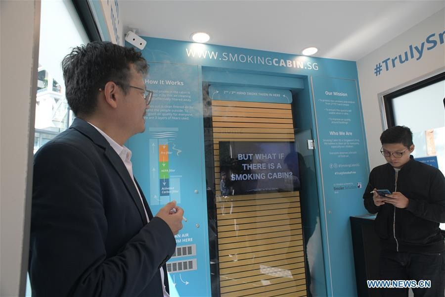 Men smoke inside a smoking cabin in Singapore on May 21, 2019. Singapore\'s first smoking cabin was launched on Tuesday. The air-conditioned cabin measures 4.8 square metres in size, that allows a maximum of 10 users at one time, and uses 3 filters to filter the air inside. (Xinhua/Then Chih Wey)