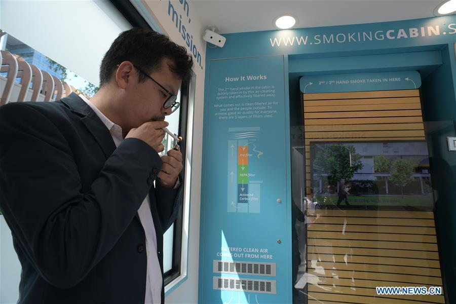 A man smokes inside a smoking cabin in Singapore on May 21, 2019. Singapore\'s first smoking cabin was launched on Tuesday. The air-conditioned cabin measures 4.8 square metres in size, that allows a maximum of 10 users at one time, and uses 3 filters to filter the air inside. (Xinhua/Then Chih Wey)