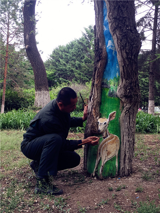 eng Shuxuan paints a deer on a tree trunk in the Zoological and Botanical Garden in Changchun, capital of Northeast China\'s Jilin Province, on Tuesday.  (Photo/chinadaily.com.cn)