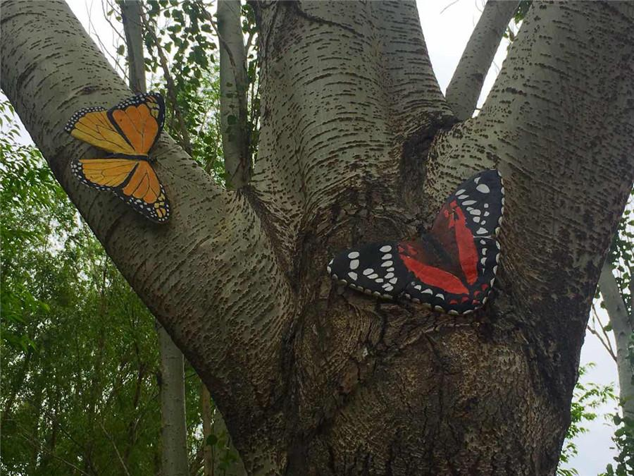 A tree trunk is painted with butterflies in the Zoological and Botanical Garden in Changchun, capital of Northeast China\'s Jilin Province.  (Photo/chinadaily.com.cn)