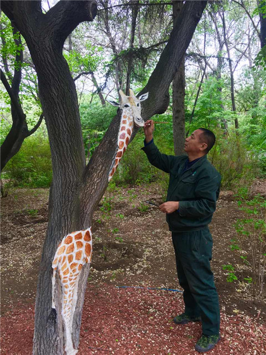 Feng Shuxuan paints a giraffe on a tree trunk in the Zoological and Botanical Garden in Changchun. (Photo/chinadaily.com.cn)