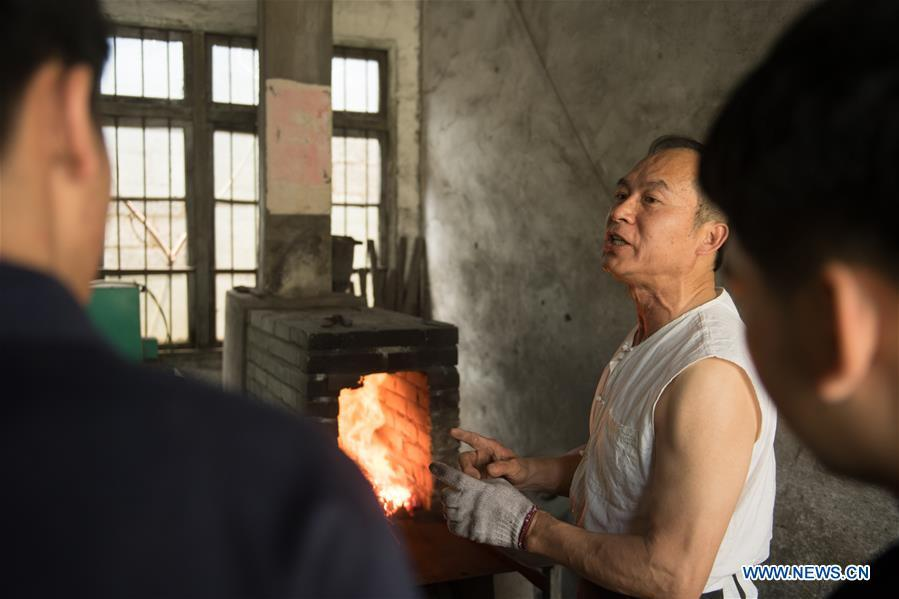 Zheng Guorong teaches skills of sword making to his apprentices at Guyue Sword Studio in Longquan, east China\'s Zhejiang Province, May 21, 2019. For centuries, Longquan has been famed for its sword making industry. Zheng Guorong, 55, an intangible cultural heritage inheritor in Longquan Sword making, has been making sword for more than 30 years. Zheng regards sword as a symbol of spirit and devotes all to his career with awe. In his studio, the whole process of making a single sword takes two to three months, with steps including forming an idea, designing the sketch, preparing material and the final making and assembling. After setting up his studio, Zheng has trained more than 20 apprentices, who have all become sword smiths of great reputation. The old sword smith insists that Longquan sword, with a history of more than 2,500 years, deserves to be carried on in our time, both materially and spiritually. (Xinhua/Weng Xinyang)