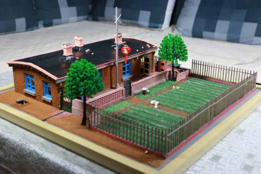 A scene from a miniature rammed-earth house, or gandalei, created by Wang Tao. (Photo provided to chinadaily.com.cn)  Wang Tao from Daqing, a city of Northeast China's Heilongjiang Province, recently finished landscape artwork on a miniature version of a rammed-earth house or gandalei, a type of traditional rural house locals lived in during the 20th century.  The house, built using double-boards with mud, is warm in winter and cool in summer.  The 41-year-old civil servant spent seven weeks creating the miniature, hoping to preserve the good memories of his childhood in the house, located in Hongqi village in Daqing.  \
