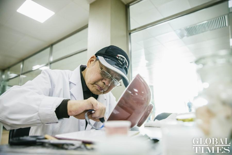 Wang Mian, Chinese ceramics repair expert, repairs a red glaze bowl used in the Qing Dynasty (1644-1911) at Yuanmingyuan Park. (Photo: Li Hao/GT)