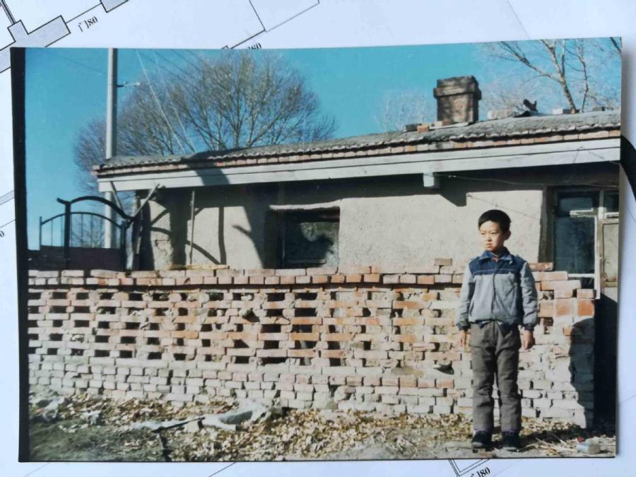 An old photo shows Wang Tao standing in front of the rammed-earth house he lived in as a child. (Photo provided to chinadaily.com.cn)