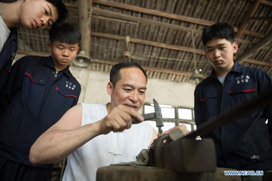 Zheng Guorong refines billet at Guyue Sword Studio in Longquan, east China\'s Zhejiang Province, May 21, 2019. For centuries, Longquan has been famed for its sword making industry. Zheng Guorong, 55, an intangible cultural heritage inheritor in Longquan Sword making, has been making sword for more than 30 years. Zheng regards sword as a symbol of spirit and devotes all to his career with awe. In his studio, the whole process of making a single sword takes two to three months, with steps including forming an idea, designing the sketch, preparing material and the final making and assembling. After setting up his studio, Zheng has trained more than 20 apprentices, who have all become sword smiths of great reputation. The old sword smith insists that Longquan sword, with a history of more than 2,500 years, deserves to be carried on in our time, both materially and spiritually. (Xinhua/Weng Xinyang)