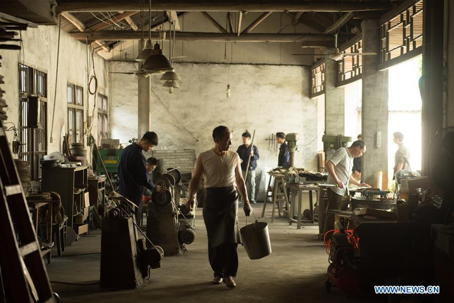 Zheng Guorong (C) and his apprentices work at Guyue Sword Studio in Longquan, east China\'s Zhejiang Province, May 21, 2019. For centuries, Longquan has been famed for its sword making industry. Zheng Guorong, 55, an intangible cultural heritage inheritor in Longquan Sword making, has been making sword for more than 30 years. Zheng regards sword as a symbol of spirit and devotes all to his career with awe. In his studio, the whole process of making a single sword takes two to three months, with steps including forming an idea, designing the sketch, preparing material and the final making and assembling. After setting up his studio, Zheng has trained more than 20 apprentices, who have all become sword smiths of great reputation. The old sword smith insists that Longquan sword, with a history of more than 2,500 years, deserves to be carried on in our time, both materially and spiritually. (Xinhua/Weng Xinyang)