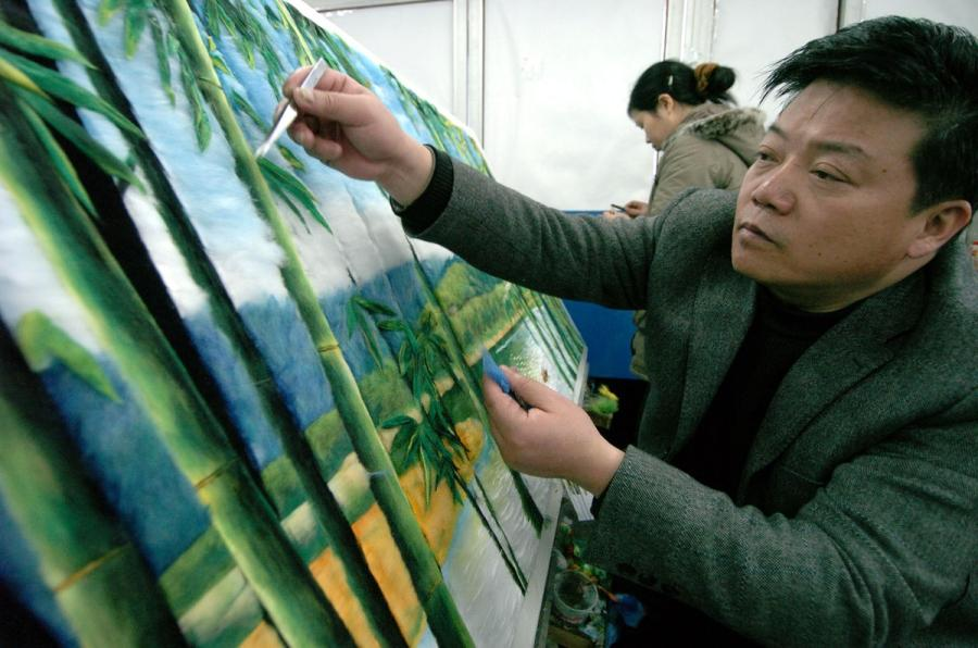 A file photo of artist Yuan Hongbin, 61, who can replicate almost any painting using cotton. (Photo/Xinhua)