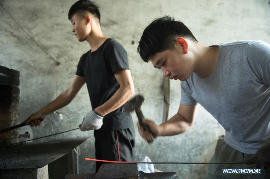Apprentices of Zheng Guorong practice sword making at Guyue Sword Studio in Longquan, east China\'s Zhejiang Province, May 21, 2019. For centuries, Longquan has been famed for its sword making industry. Zheng Guorong, 55, an intangible cultural heritage inheritor in Longquan Sword making, has been making sword for more than 30 years. Zheng regards sword as a symbol of spirit and devotes all to his career with awe. In his studio, the whole process of making a single sword takes two to three months, with steps including forming an idea, designing the sketch, preparing material and the final making and assembling. After setting up his studio, Zheng has trained more than 20 apprentices, who have all become sword smiths of great reputation. The old sword smith insists that Longquan sword, with a history of more than 2,500 years, deserves to be carried on in our time, both materially and spiritually. (Xinhua/Weng Xinyang)