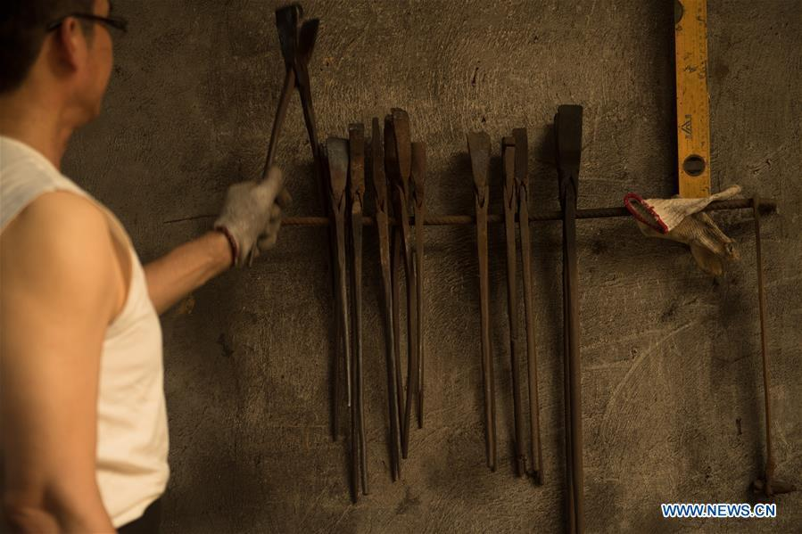 Zheng Guorong works at Guyue Sword Studio in Longquan, east China\'s Zhejiang Province, May 21, 2019. For centuries, Longquan has been famed for its sword making industry. Zheng Guorong, 55, an intangible cultural heritage inheritor in Longquan Sword making, has been making sword for more than 30 years. Zheng regards sword as a symbol of spirit and devotes all to his career with awe. In his studio, the whole process of making a single sword takes two to three months, with steps including forming an idea, designing the sketch, preparing material and the final making and assembling. After setting up his studio, Zheng has trained more than 20 apprentices, who have all become sword smiths of great reputation. The old sword smith insists that Longquan sword, with a history of more than 2,500 years, deserves to be carried on in our time, both materially and spiritually. (Xinhua/Weng Xinyang)