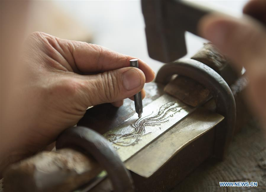 Zheng Guorong carves patten of a phoenix on a sword at Guyue Sword Studio in Longquan, east China\'s Zhejiang Province, May 21, 2019. For centuries, Longquan has been famed for its sword making industry. Zheng Guorong, 55, an intangible cultural heritage inheritor in Longquan Sword making, has been making sword for more than 30 years. Zheng regards sword as a symbol of spirit and devotes all to his career with awe. In his studio, the whole process of making a single sword takes two to three months, with steps including forming an idea, designing the sketch, preparing material and the final making and assembling. After setting up his studio, Zheng has trained more than 20 apprentices, who have all become sword smiths of great reputation. The old sword smith insists that Longquan sword, with a history of more than 2,500 years, deserves to be carried on in our time, both materially and spiritually. (Xinhua/Weng Xinyang)