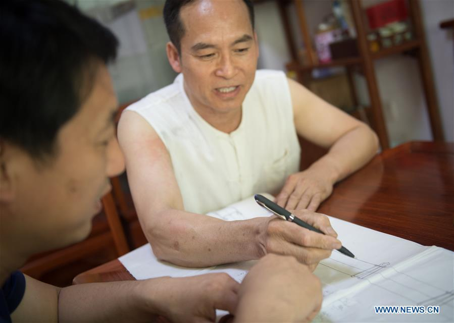 Zheng Guorong (R) discusses the design of sword with a customer at Guyue Sword Studio in Longquan, east China\'s Zhejiang Province, May 21, 2019. For centuries, Longquan has been famed for its sword making industry. Zheng Guorong, 55, an intangible cultural heritage inheritor in Longquan Sword making, has been making sword for more than 30 years. Zheng regards sword as a symbol of spirit and devotes all to his career with awe. In his studio, the whole process of making a single sword takes two to three months, with steps including forming an idea, designing the sketch, preparing material and the final making and assembling. After setting up his studio, Zheng has trained more than 20 apprentices, who have all become sword smiths of great reputation. The old sword smith insists that Longquan sword, with a history of more than 2,500 years, deserves to be carried on in our time, both materially and spiritually. (Xinhua/Weng Xinyang)